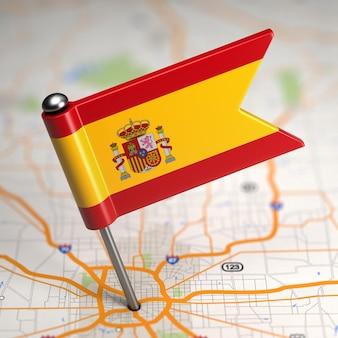 Pequeña bandera de españa sobre un fondo de mapa con enfoque selectivo.