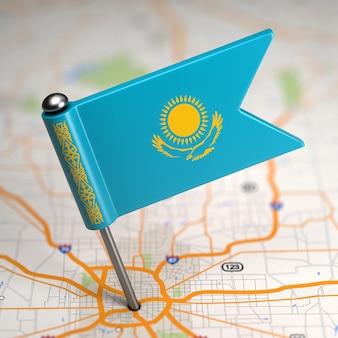 Pequeña bandera de kazajstán sobre un fondo de mapa con enfoque selectivo.