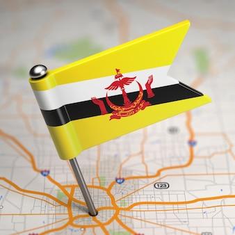 Pequeña bandera de la nación de brunei, morada de la paz sobre un fondo de mapa con enfoque selectivo.