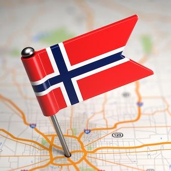 Pequeña bandera de noruega pegada en el fondo del mapa con enfoque selectivo.