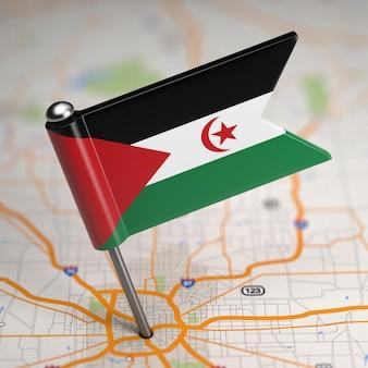 Pequeña bandera de la república árabe saharaui democrática sobre un fondo de mapa con enfoque selectivo.