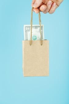Una pequeña bolsa de papel para ayuda financiera y soporte hecha de papel con los dólares estadounidenses sobre un fondo azul. el concepto de apoyo financiero insignificante en los negocios,