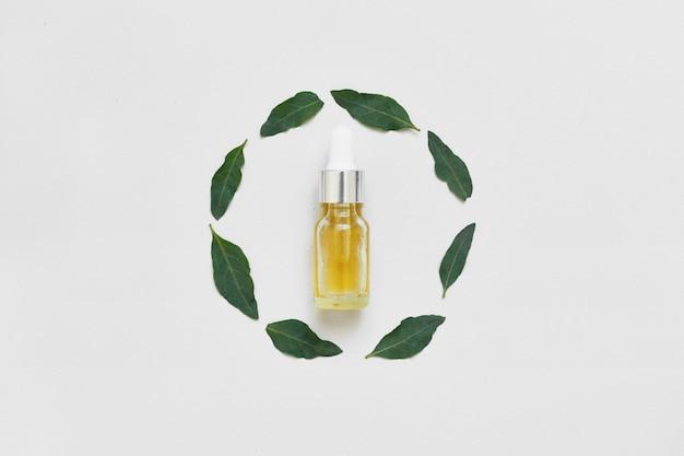 Pequeña botella de aceite esencial y hojas frescas sobre fondo blanco. estilo de vida holístico