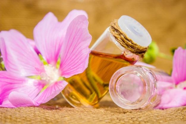 Una pequeña botella de aceite esencial de malva a base de hierbas, tintura, extracto
