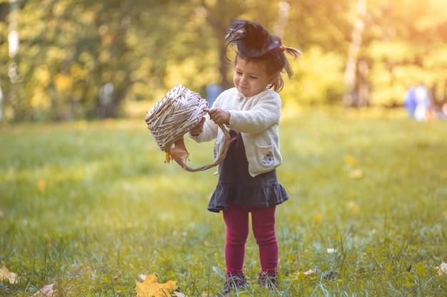 Pequeña bruja linda voltea una canasta y vierte hojas de otoño en el parque.
