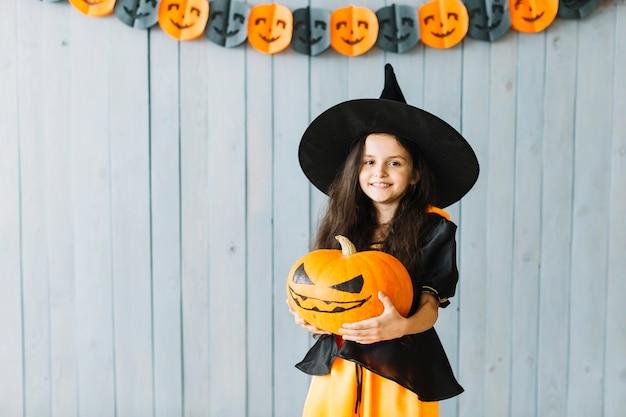 Pequeña bruja sonriendo en la fiesta de halloween