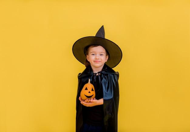 Pequeña bruja sonriente con un sombrero y cabo tiene una calabaza y sonríe en un amarillo aislado