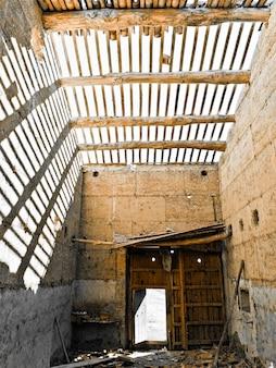 Pequeña cabaña de tierra con el techo destruido sin tejas
