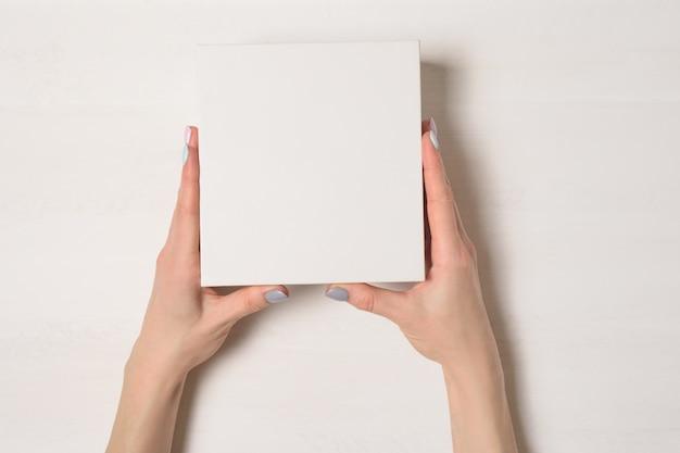 Pequeña caja de cartón blanca en manos femeninas.