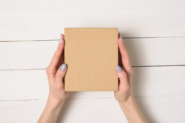 Pequeña caja de cartón en manos femeninas. vista superior. mesa blanca