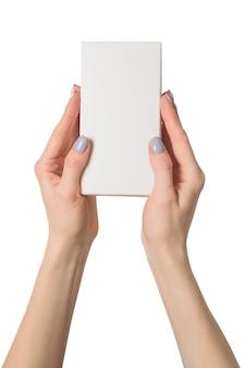 Pequeña caja rectangular en manos femeninas. vista superior. aislar