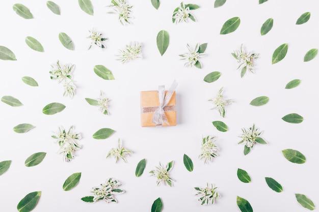 Pequeña caja con un regalo y cinta sobre una mesa blanca.
