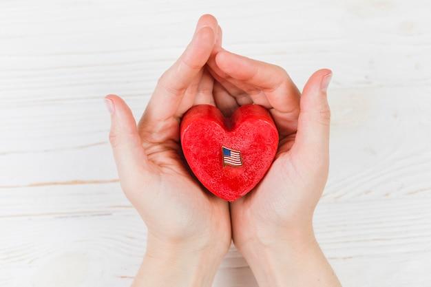 Pequeña caja de regalo con forma de corazón en las manos.