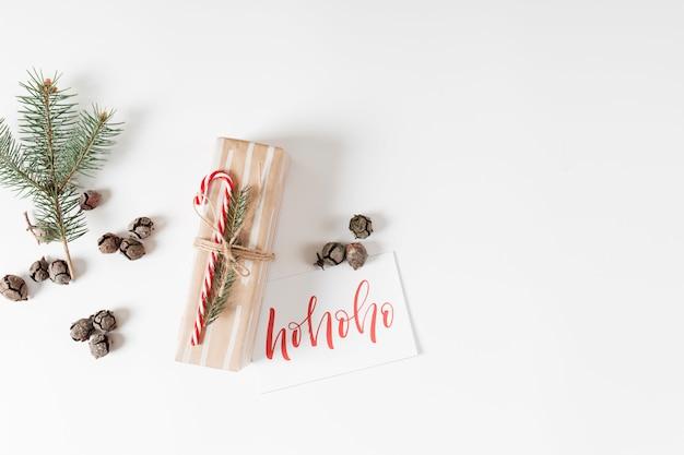 Pequeña caja de regalo con inscripción ho ho ho sobre papel.