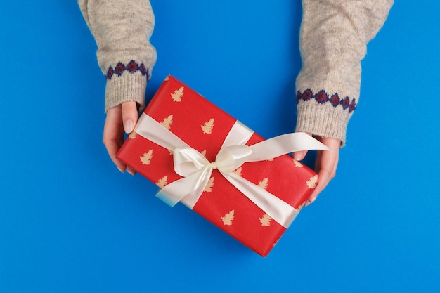 Pequeña caja de regalo en manos femeninas sobre fondo azul, vista desde arriba