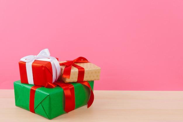 Pequeña caja de regalo sobre fondo rosa pastel