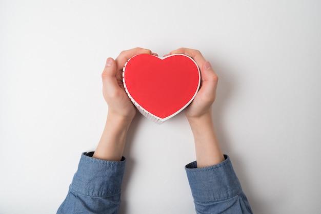Pequeña caja roja en forma de corazón en mano masculina aislada en