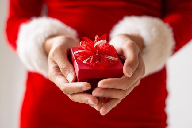 Pequeña caja roja presente con lazo en manos femeninas.