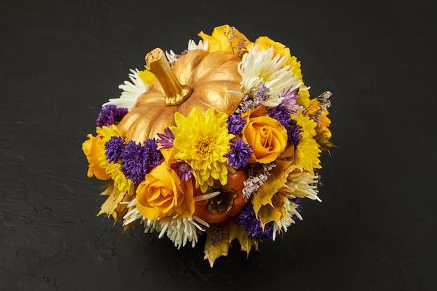 Pequeña calabaza decorada con flores amarillas y azules.
