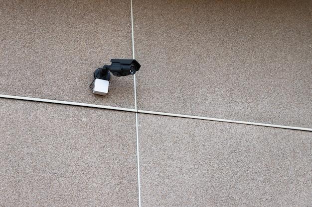 Pequeña cámara de vigilancia exterior fijada a la pared.