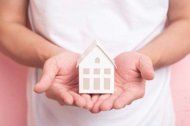 Pequeña casa blanca en mano humana