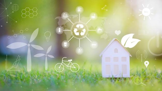 Pequeña casa blanca sobre fondo verde con iconos de conservación ecológica, concepto de tecnología de desarrollo ecológico