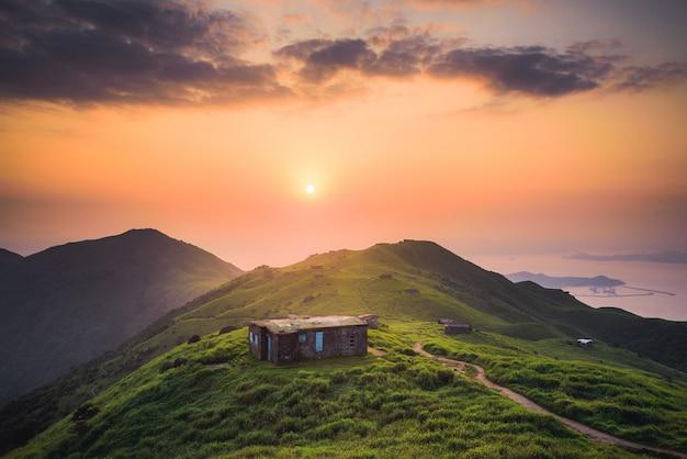 Pequeña casa construida en una tranquila colina verde en lo alto de las montañas