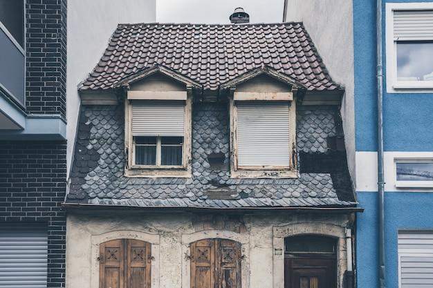 Pequeña casa envejecida y antigua entre dos casas nuevas y modernas