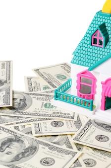 Pequeña casa de juguete de pie en billetes de cien dólares