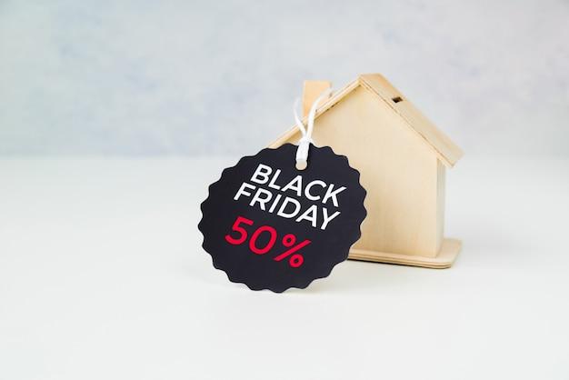 Pequeña casa de madera con etiqueta de viernes negro