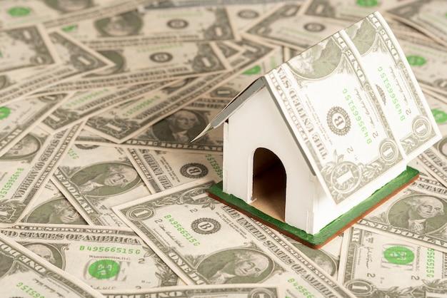 Pequeña casa modelo de juguete rodeada de dinero
