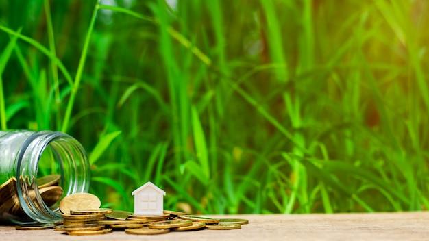 Pequeña casa en la pila de monedas de oro en el jardín