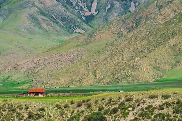 Pequeña casa de pueblo solitario con techo rojo cerca del precipicio cerca del pie de la montaña.