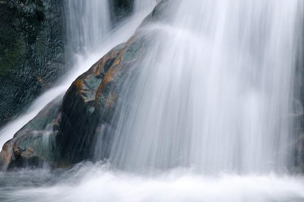 Una pequeña cascada activa. arroyo de montaña limpio, paisaje nevado de invierno, vida silvestre