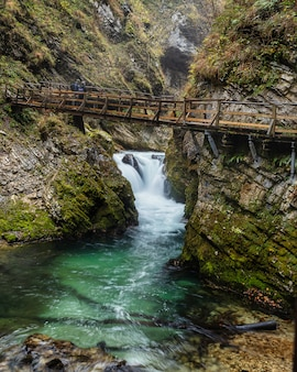 Pequeña cascada y aguas color esmeralda del desfiladero de vintgar con camino elevado de madera con vistas, eslovenia