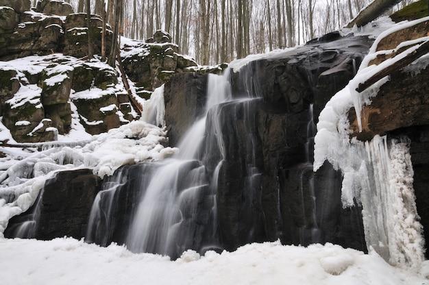 Una pequeña cascada de montaña cubierta de nieve.