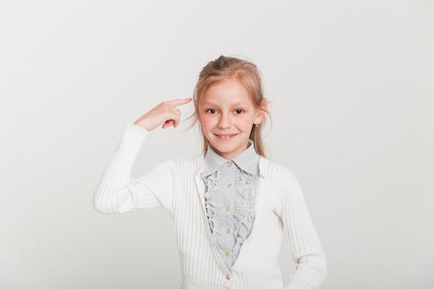 Pequeña chica apuntando hacia su cabeza