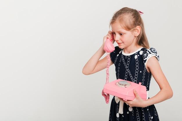 Pequeña chica llamando en teléfono vintage