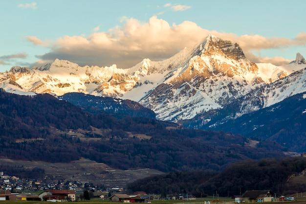 Pequeña ciudad al pie de la magnífica cordillera de los alpes, suiza. vida tranquila en la escena de picos fantásticos cubiertos de nieve brillante y bosque verde oscuro bajo un cielo azul con nubes blancas hinchadas.