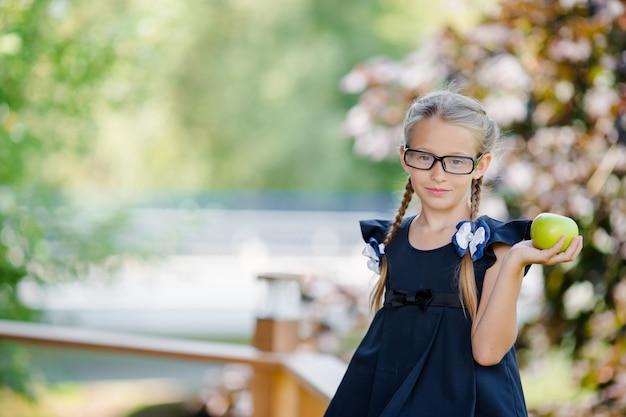 Pequeña colegiala adorable con la manzana verde al aire libre. concepto de regreso a la escuela