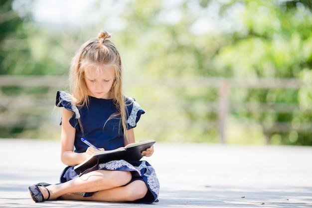 Pequeña colegiala adorable con las notas y los lápices al aire libre. de vuelta a la escuela.