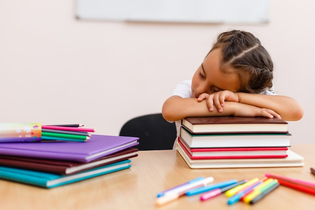 Pequeña colegiala dormir en el aula cerca de la pizarra
