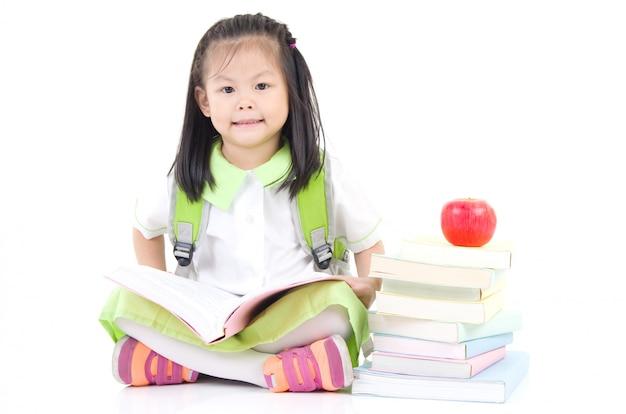 Pequeña colegiala feliz con los libros aislados en el fondo blanco