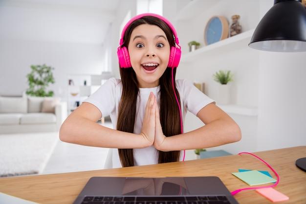 Pequeña colegiala hacer videollamada en la computadora portátil