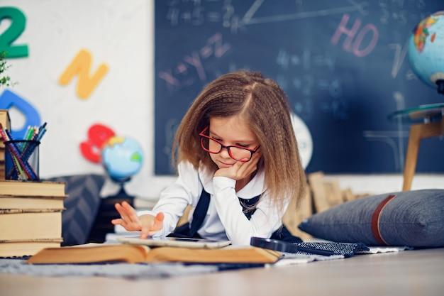 Pequeña colegiala inteligente con tableta digital en un aula.