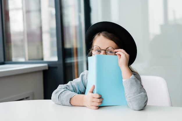 Pequeña colegiala linda en anteojos y sombrero asoma de libro abierto en la lección de literatura mientras está sentado en el escritorio