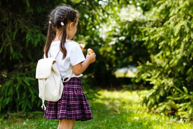 Pequeña colegiala que come los croissants en el parque. regreso a la escuela al aire libre