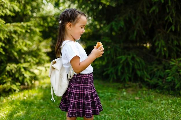 Pequeña colegiala que come los cruasanes en el parque. regreso a la escuela al aire libre