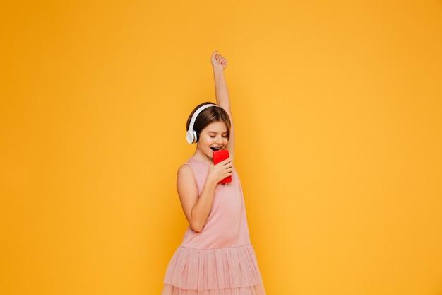Pequeña dama en auriculares cantando en smartphone aislado