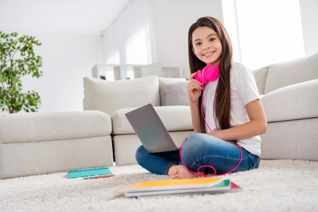 Pequeña dama de ensueño usar auriculares relajarse sentarse alfombra con la computadora portátil en las rodillas